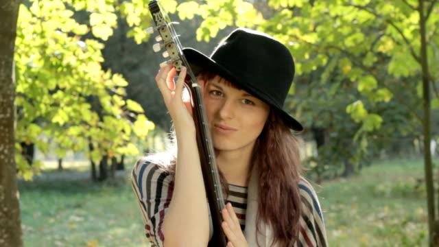 vídeos y material grabado en eventos de stock de joven mujer coqueteando y posando en el parque, con guitarra, sonriendo al aire libre. - guitarrista