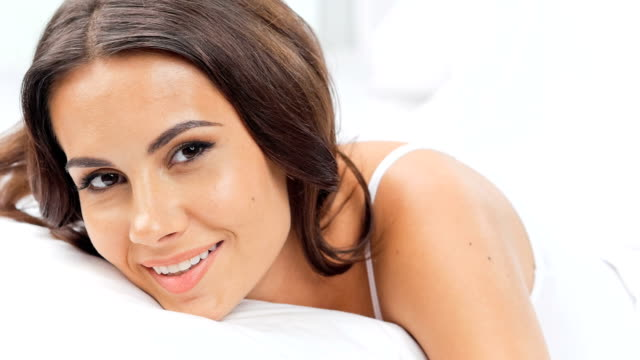 Young woman flirting smiling on bed