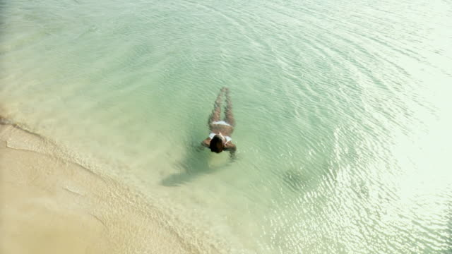WS Young woman floating in water on beach / Scarborough, Tobago, Trinidad And Tobago
