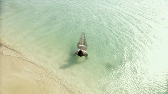 ws young woman floating in water on beach / scarborough, tobago, trinidad and tobago  - auf dem wasser treiben stock-videos und b-roll-filmmaterial