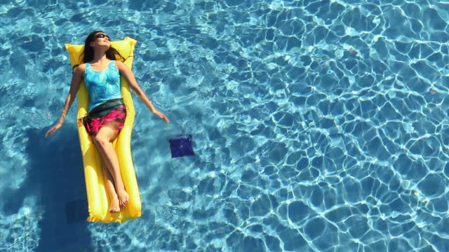 young woman floating on a inflatable bed in a swimming pool - inflatable raft stock videos and b-roll footage