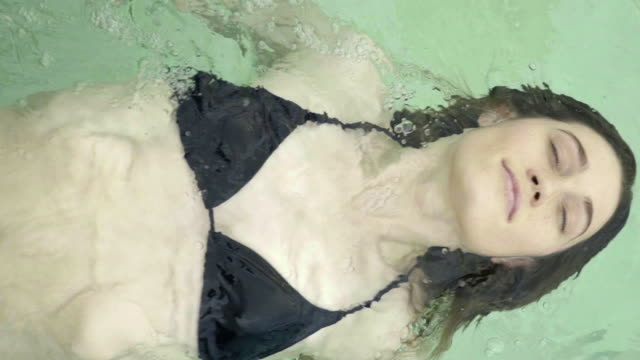 stockvideo's en b-roll-footage met young woman floating on back in pool with eyes closed - buitenbad
