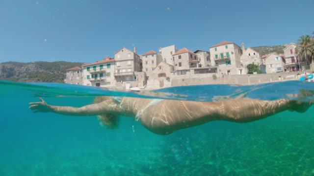 vídeos y material grabado en eventos de stock de ms joven mujer flotando en la espalda en el soleado mar adriático,croacia - flotar sobre agua