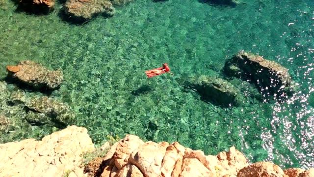 junge frau auf pool-matratze im ozean schwimmen - sardinien stock-videos und b-roll-filmmaterial