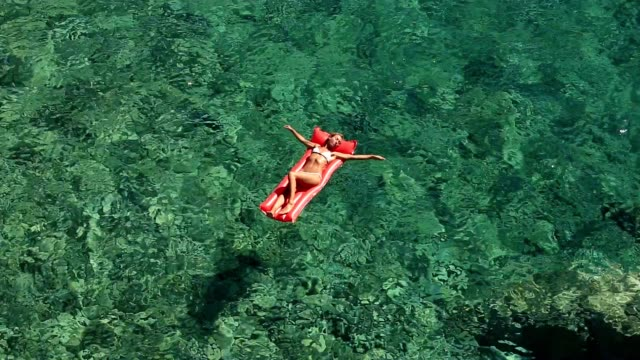 young woman floating on pool mattress in the ocean - galleggiare sull'acqua video stock e b–roll