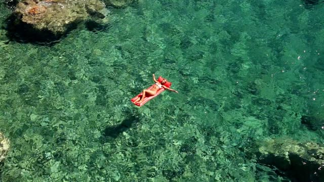 young woman floating on pool mattress in the ocean - abbronzatura video stock e b–roll