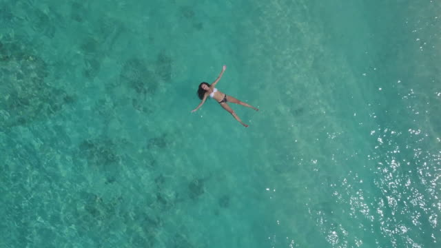 young woman floating on water near gili island coastline - floating on water stock videos & royalty-free footage