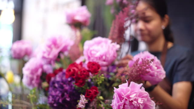 young woman florist working with flowers. - bunch of flowers stock videos and b-roll footage