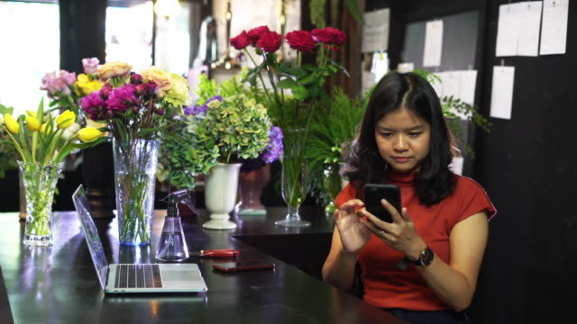 Young woman florist working with smart phone.