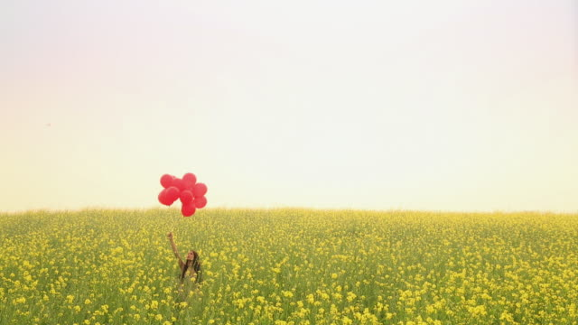 Young woman flying balloons in the mustard field, Haryana, India
