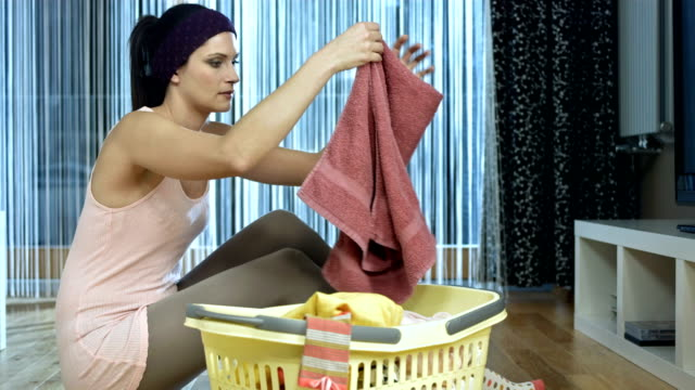 vídeos de stock e filmes b-roll de carrinho de hd: jovem mulher dobrar roupa - afazeres domésticos
