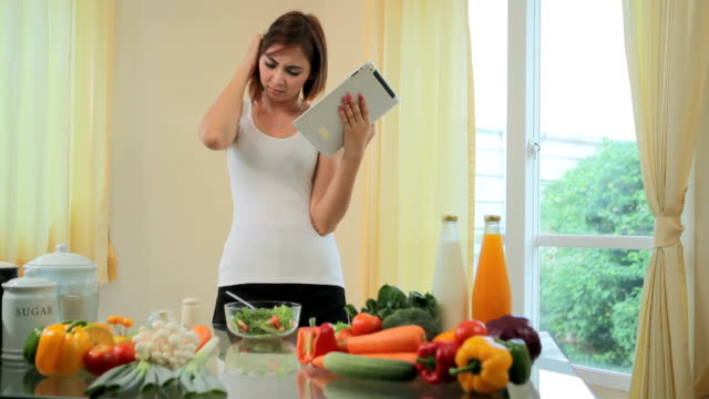 Young woman Following Recipe On Digital Tablet