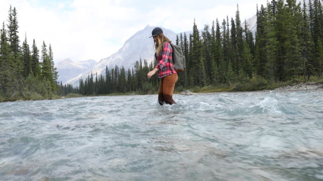 A young woman forging the Bow River on a hike into Hector Lake.