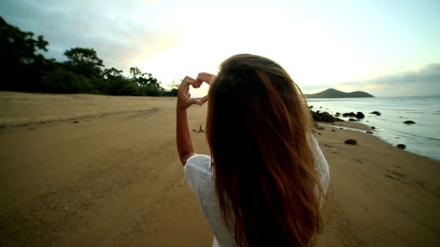 Young woman frames sunset on beach into heart shape