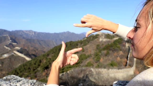 Young woman framing Great Wall of China with fingers