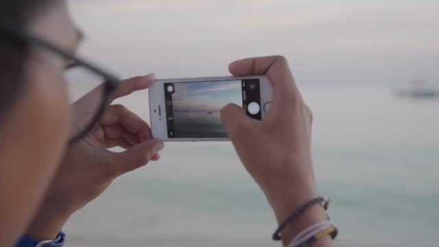 vídeos de stock, filmes e b-roll de young woman from philippines taking picture at bantaya beach - ocidentalização