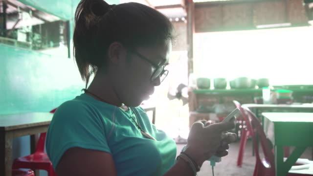 vídeos de stock, filmes e b-roll de young woman from philippines using cellphone at indoors restaurant - ocidentalização