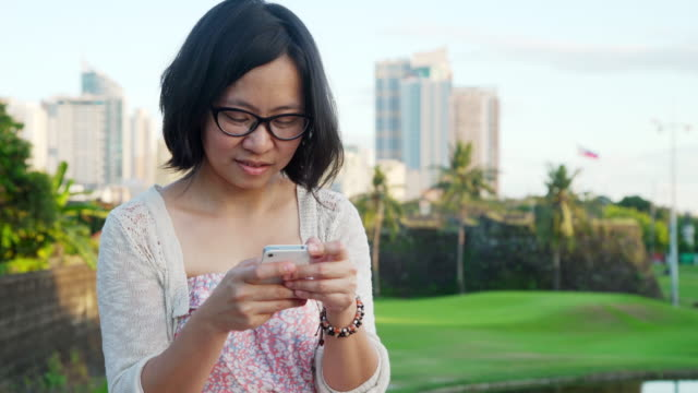 young woman from philippines using cellphone at intramuros manila - links golf stock videos & royalty-free footage