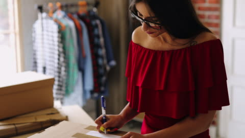 young woman fulfilling online order - button down shirt stock videos & royalty-free footage