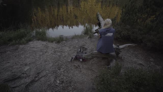 Junge Frau blickt über Waldteich