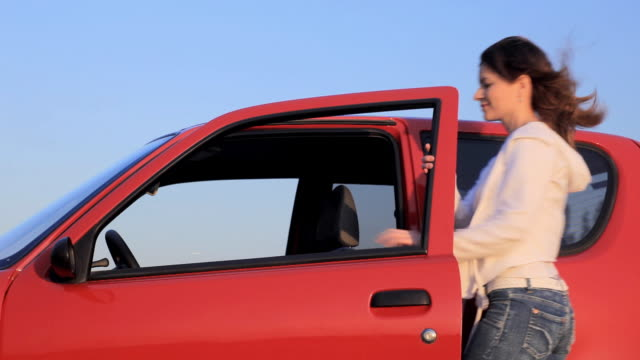 Young woman geting into the car  and driving.