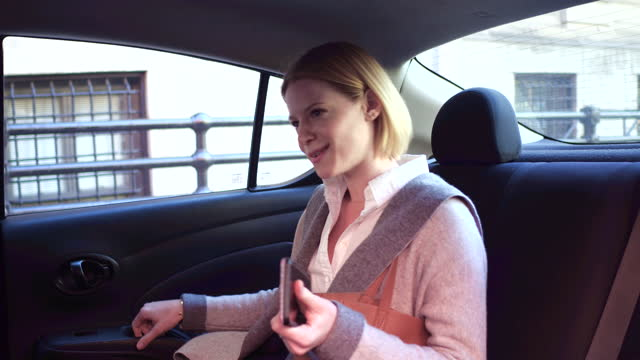 young woman gets into back seat of car, daytime - car interior stock videos & royalty-free footage