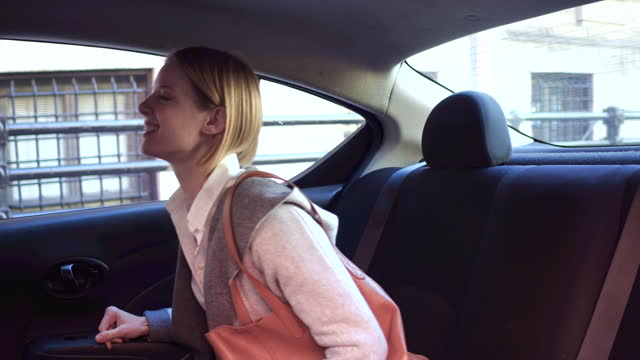 young woman gets into back seat of car, daytime - handbag stock videos and b-roll footage