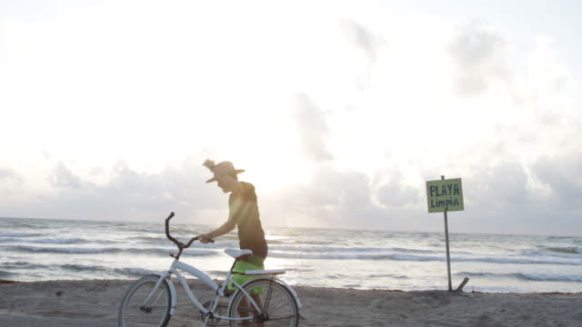 WS Young woman gets on a bicycle and rides away from the beach.