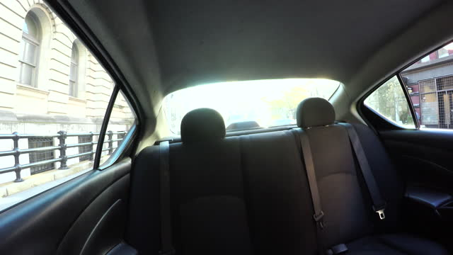 Young woman gets out of car from back seat, daytime