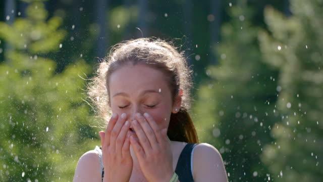 stockvideo's en b-roll-footage met jonge vrouw wordt besproeid met water, reageert - langzaam
