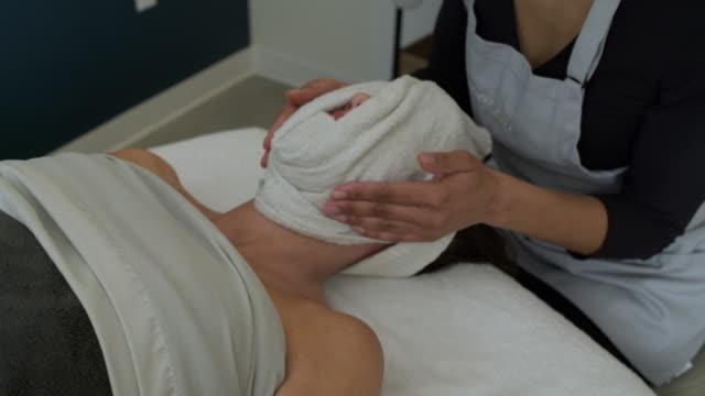 young woman getting a facial treatment in a spa - タオルにくるまる点の映像素材/bロール