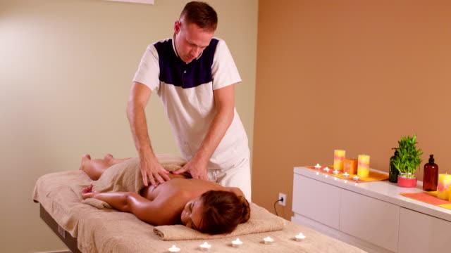 vídeos y material grabado en eventos de stock de mujer joven volver masaje en el spa de salud - articulación humana
