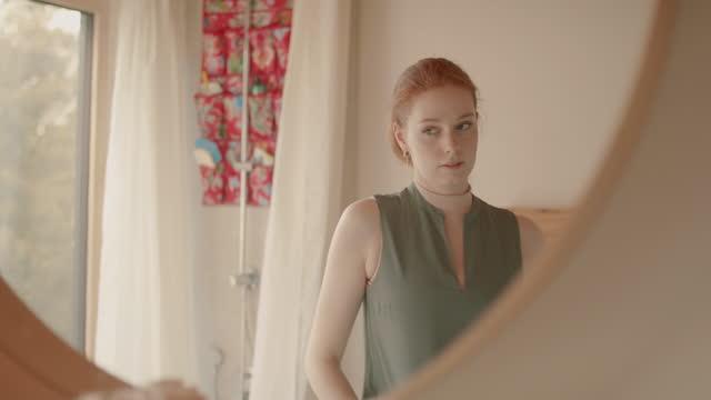 vídeos de stock e filmes b-roll de young woman getting dressed in front of mirror in bathroom in morning - espelho
