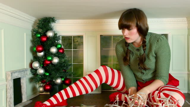 Young woman getting frustrated trying to decorate christmas tree in small room