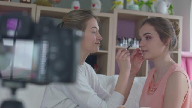 若い女性は、ビデオを撮影しながら美容ブロガーによって彼女のメイクアップを取得します - 美容専門家点の映像素材/bロール