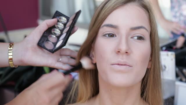 vidéos et rushes de une jeune femme se son maquillage fait - pinceau à blush