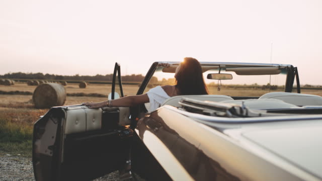 ms young woman getting into convertible parked at sunny, rural hay field - hay isolated stock videos & royalty-free footage