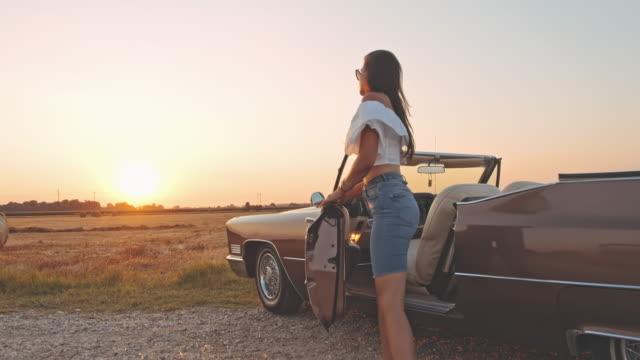 slo mo junge frau, die aus cabrio am ländlichen sonnenuntergang am straßenrand geparkt - aussteigen stock-videos und b-roll-filmmaterial