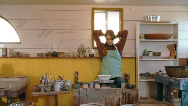 young woman getting ready to create in her studio - keramik stock-videos und b-roll-filmmaterial