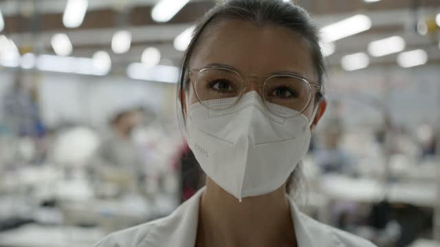 vidéos et rushes de jeune femme se préparant à travailler à une usine textile avec un masque protecteur et des lunettes tout en faisant face à l'appareil-photo - agence de design