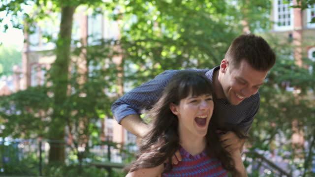 ts - young woman gives young man a piggyback in urban park - プロレスごっこ点の映像素材/bロール