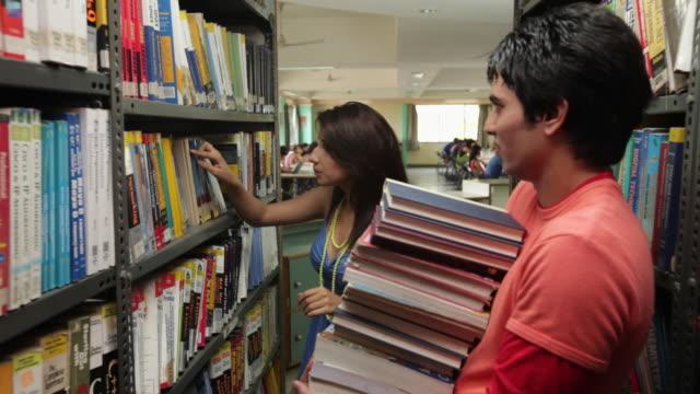 vidéos et rushes de young woman giving lots of books to his friend  - rayonnage de livre