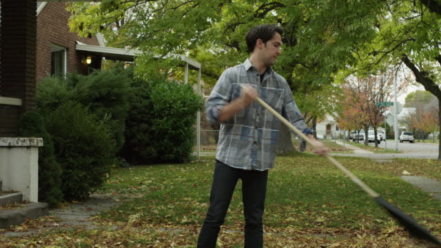 ws tu young woman giving tea mug to man raking leaves in front of house / provo, utah, usa - provo stock videos & royalty-free footage