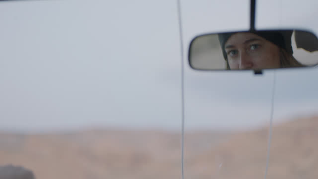 cu. young woman glances in rear view mirror and smiles as she drives through rocky moab landscape. - sideways glance stock videos & royalty-free footage