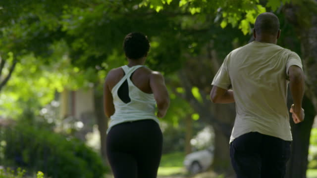 Young woman goes jogging with her father down leafy sidewalk.