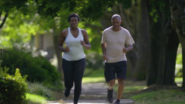 Young woman goes jogging with her father down sunny sidewalk.