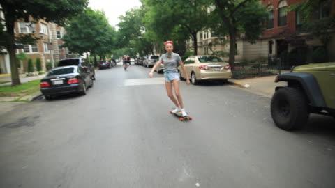 stockvideo's en b-roll-footage met a young woman goes longboard skateboarding. - skateboard