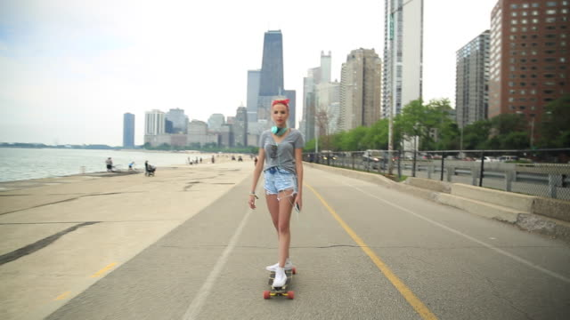 A young woman goes longboard skateboarding with the Chicago, Illinois skyline in the background.