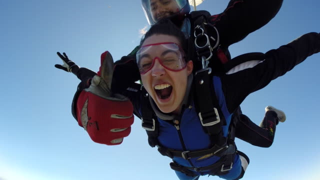 young woman goes skydiving for the first time. (audio) - eccitazione video stock e b–roll