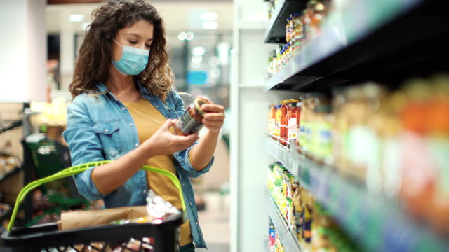 young woman going grocery shopping after business reopened during coronavirus pandemic - groceries stock videos & royalty-free footage